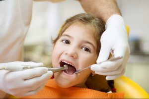 A young girl in the dental chair having her mouth checked