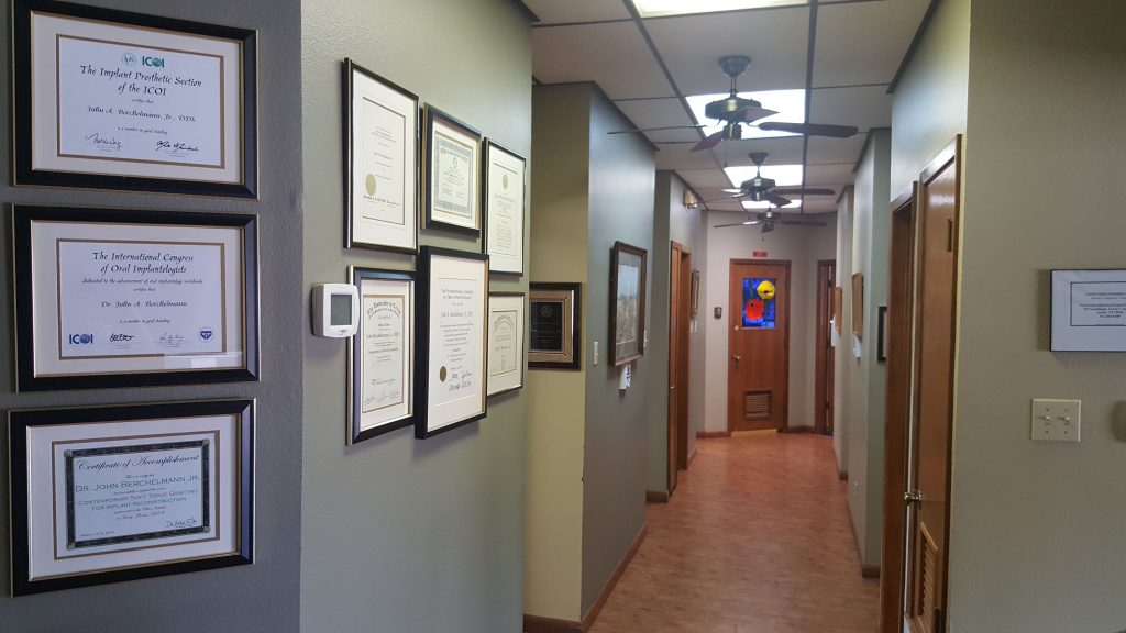 A hallway of a dental office with awards on the walls