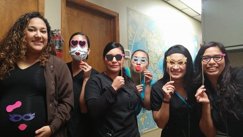 A group of women holding props in front of their faces