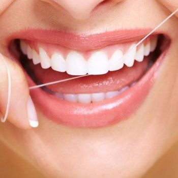 A close up of a woman flossing her teeth