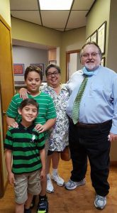 A family smiling in the hallway of the dental office