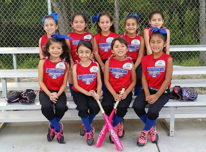 A group of young girls in their softball uniforms sitting on a bench
