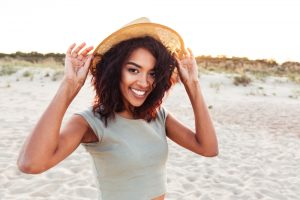 A young woman smiling and holding her hat on the beach