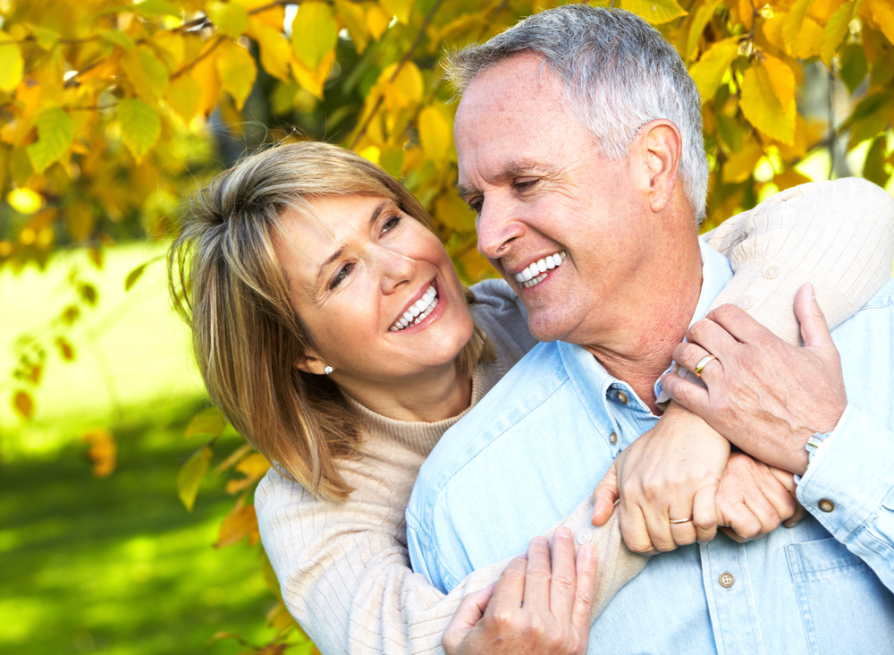 An older couple smiles. The woman is hugging the man from behind him. They're in front of a tree. Their teeth are immaculately white and straight.