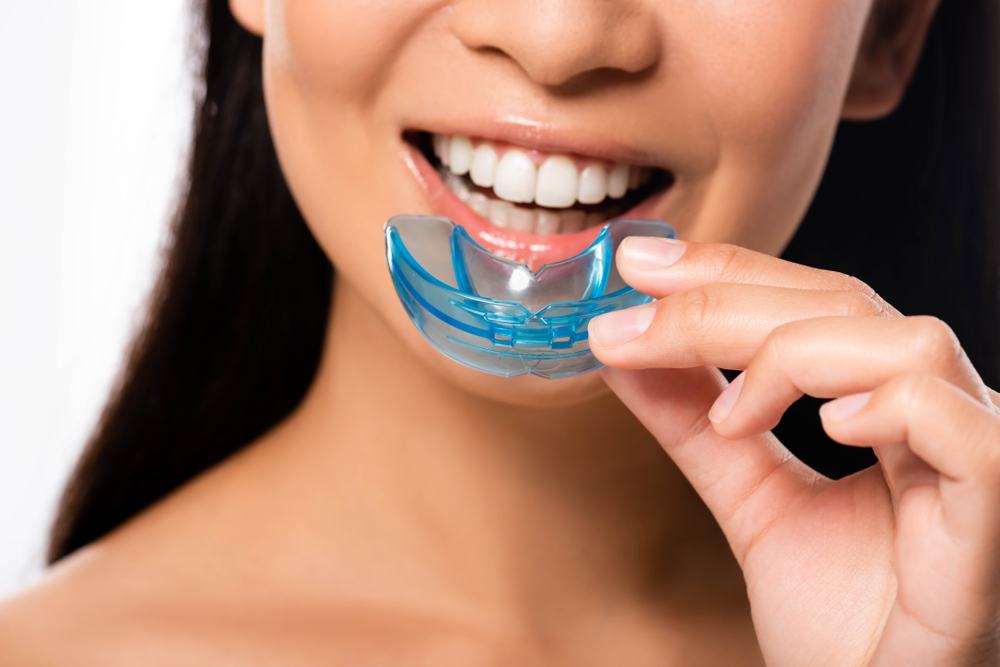 A woman smiles while holding her blue custom mouthguard in front of her face.