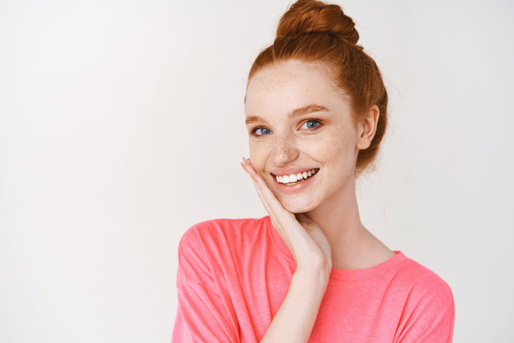 A red-haired woman with her hair in a bun smiles in front of a white background. She's wearing a pink shirt and her hand is resting on her cheek. Her teeth are white and straight.