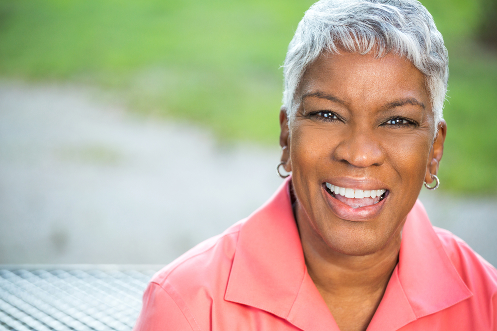 An older African American woman sits outside in a salmon colored shirt. She's smiling, and her teeth are white and straight.